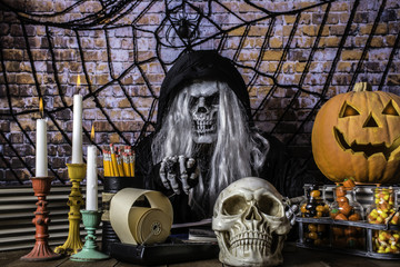 man in Grimm reaper robe scary skull mask and skeleton hands pointing at camera surrounded by skull jack o lantern burning candles Halloween candy and large spider and web