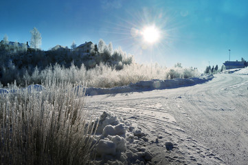 Travel to Sweden. Small, snowy winter road (Sandared). The sun is shining and the blue sky is up.
