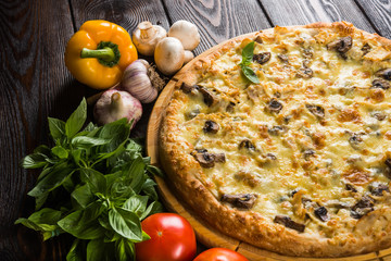 Pizza with mushrooms and cheese on a dark wooden background with fresh vegetables