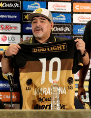 Argentinian soccer legend Diego Armando Maradona poses with the uniform of the Dorados football club during a news conference where he is presented as the new head coach of the club, in Culiacan, in the Mexican state of Sinaloa