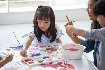 group of Cute little girl student painting  together with nursery teacher in classroom school . Happy children in a kindergarten