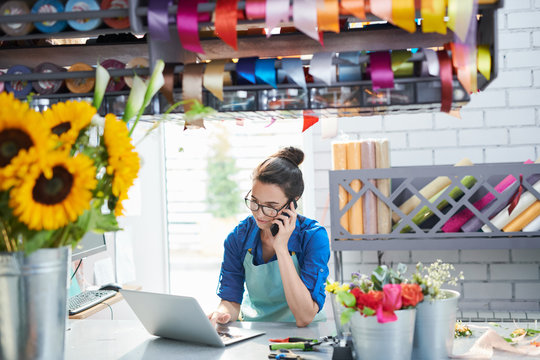 Portrait of young female businesswoman managing flower shop and speaking by phone, copy space