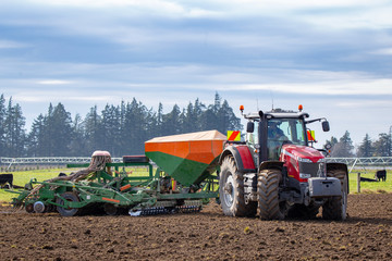 A farmer seeds his paddocks in the springtime using a pneumatic seed drill behind a red tractor