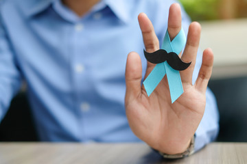 Prostate Cancer Awareness, Man hand holding light Blue Ribbon with mustache for supporting people living and illness. Men Healthcare and World cancer day concept