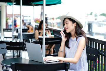 Young asian woman talking phone while working at cafe in the city outdoors background, people working outdoors with technology, lifestyle