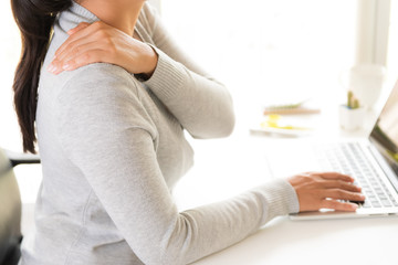 Closeup woman with hands holding her shoulder pain. Office syndrome and Health care concept.