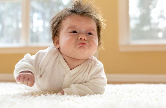Upset newborn baby boy being making a face