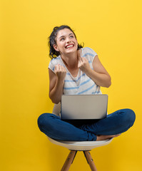 Young woman using her laptop on a yellow background
