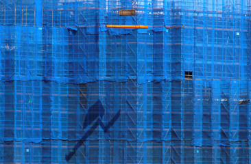 A crane lifts building materials in front of scaffolding at a construction site in central Sydney
