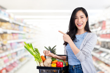 Asian woman with shopping basket full of groceries in supermarket