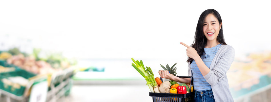 Woman with shopping basket full of groceries in supermarket banner background