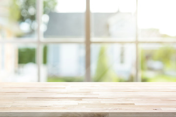 Wood table top with window and morning sunlight in background