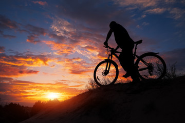 Silhouette of sports person cycling on the meadow on the beautiful sunset. Young man riding bicycle.