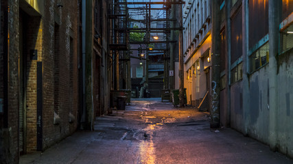 "Empty dark and scary back alley. Desolated area in one of the most vibrant cities in North America. The alley is in the vicinity of the well known ""Hastings"" St. Vancouver, British Columbia. Canada."