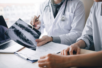Doctor pointing to the x-ray sheet and describe a viral disease or tumor to patients.