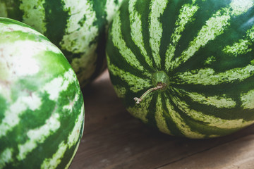 group of striped watermelons lies on wooden boards