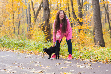 Autumn, pets, people concept - happy woman laughing with the black cat