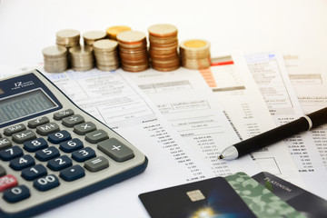 close up of a credit cards with credit card statements, pen, stack of coins and calculator on white background, financial concept, selective focus
