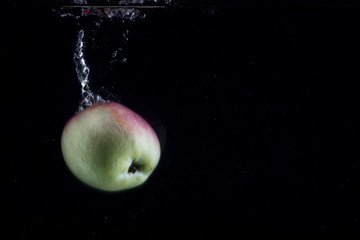 green red apple falls to the bottom on a dark background leaving a beautiful trail