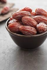 Fresh Medjool Dates in a bowl. Ramadan kareem. Black background. Top view. Copy space.