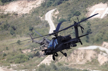 South Korean army Apache helicopters fly during a demonstration at a media event of 2018 Defense Expo Korea near the demilitarized zone separating the two Koreas in Pocheon