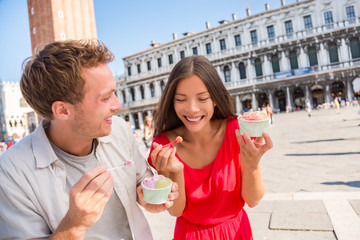 Aufkleber - Happy couple laughing eating ice cream on vacation travel in Venice, Italy. Smiling happy young couple in love having fun eating italian gelato food on San Marco Square, Venice, Italy holidays.