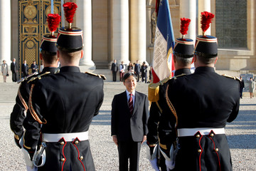 Japan's Crown Prince Naruhito reviews troops during a ceremony at the Hotel des Invalides in Paris