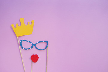 Colorful photo booth props glasses, lips, crown and on pink background with copyspace. Set of party props.