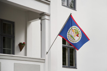 Belize flag. Belize flag hanging on a pole in front of the house. National flag of waving on a home displaying on a pole on a front door of a building. Flag raised at a full staff.