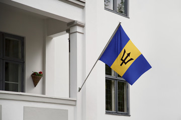 Barbados flag.  Barbados flag hanging on a pole in front of the house. National flag of waving on a home displaying on a pole on a front door of a building. Flag raised at a full staff.