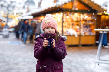 Little cute kid girl with cup of steaming hot chocolate or children punch. Happy child on Christmas market in Germany. Traditional leisure for families on xmas.