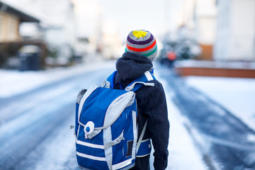 Little school kid boy of elementary class walking to school during snowfall. Happy child having fun. Street of city with cars and traffic. Student with backpack or satchel in colorful winter clothes.