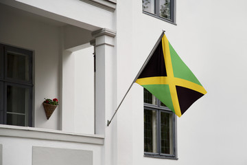 Jamaica flag. Jamaica flag hanging on a pole in front of the house. National flag of waving on a home displaying on a pole on a front door of a building. Flag raised at a full staff.