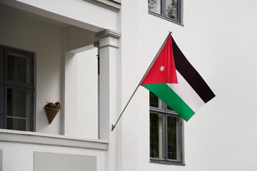 Jordan flag.  Jordan flag hanging on a pole in front of the house. National flag of waving on a home displaying on a pole on a front door of a building. Flag raised at a full staff.