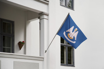 Louisiana flag.  Louisiana state flag hanging on a pole in front of the house. State flag waving on a home displaying on a pole on a front door of a building.Flag raised at a full staff.