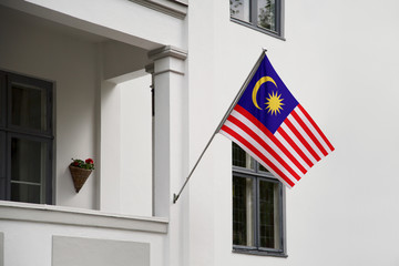 Malaysia flag.  Malaysia flag hanging on a pole in front of the house. National flag of waving on a home displaying on a pole on a front door of a building. Flag raised at a full staff.