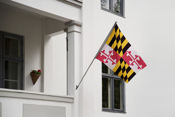 Maryland flag.  Maryland state flag hanging on a pole in front of the house. State flag waving on a home displaying on a pole on a front door of a building.Flag raised at a full staff.