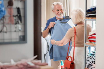 Try this quality. Waist up of pleased grey haired husband showing blue pullover to his lovely wife while being proud with his choice