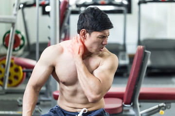 Asian man have injury muscle in a neck pain after workout in gym,Healthcare concept