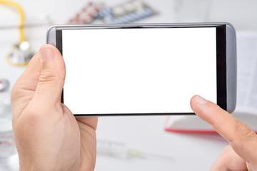 Smartphone mit leerem Display mit medizinischem Bedarf im Hintergrund