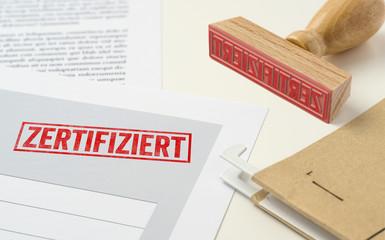 Roter Stempel auf Unterlagen - Zertifiziert