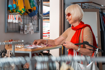 Shopping process. Profile of elderly fashionable grey haired woman choosing additional garment for her new dress while expressing interest on her face