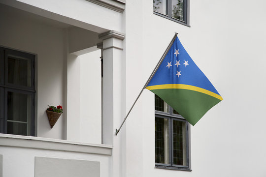 Solomon Islands flag.  Solomon Islands flag hanging on a pole in front of the house. National flag of waving on a home displaying on a pole on a front door of a building. Flag raised at a full staff.