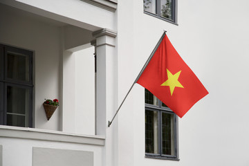 Vietnam flag.  Vietnam flag hanging on a pole in front of the house. National flag of  Vietnam waving on a home displaying on a pole on a front door of a building. Flag raised at a full staff.