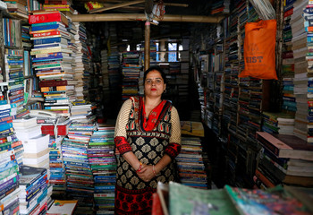Ishwori Sapkota stand in front of her secondhand bookstall where people can buy and sell used books in Kathmandu