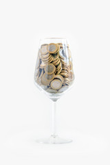 glass of wine with euro coins, cup filled with money on white background