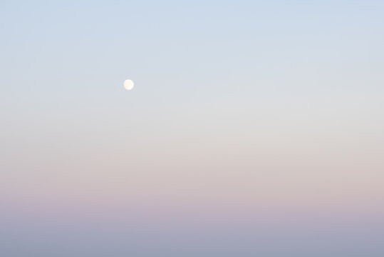 The full moon on a blue sky with pink pastel shades