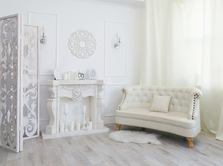 White interior of a photo studio with a fireplace and a sofa in the center