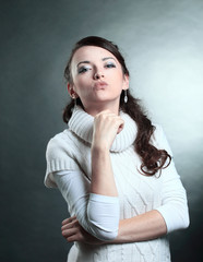 closeup.beautiful young woman in white sweater making a kiss.isolated