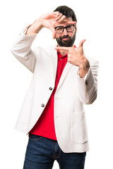 Brunette man with glasses focusing with his fingers on white background